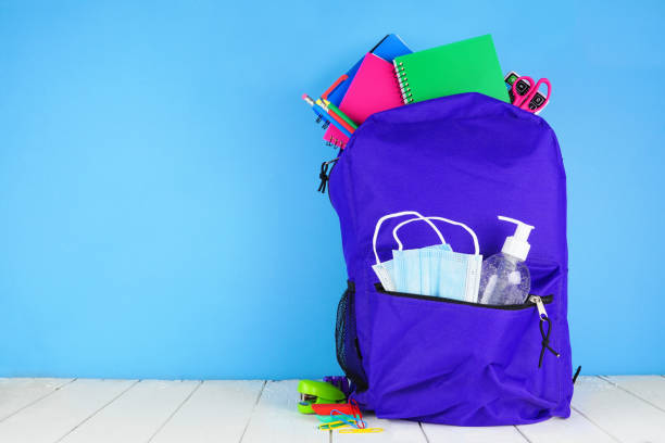 Backpack full of school supplies and COVID 19 prevention supplies against a blue background Backpack full of school supplies and COVID 19 prevention supplies. Blue background. Back to school during pandemic concept. back to school stock pictures, royalty-free photos & images