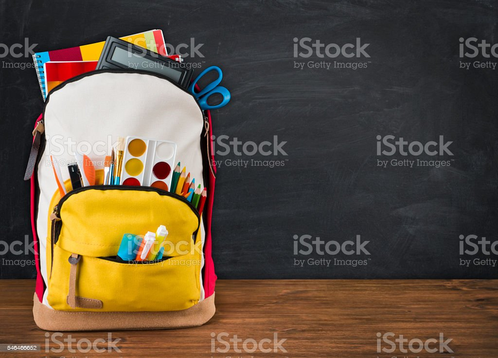 Backpack full of school supplies over black school board background stock photo