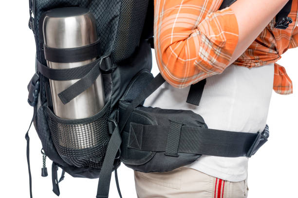 backpack full of tourists at the waist with a thermos close up stock photo