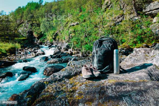 backpack, hiking boots and thermos in nature