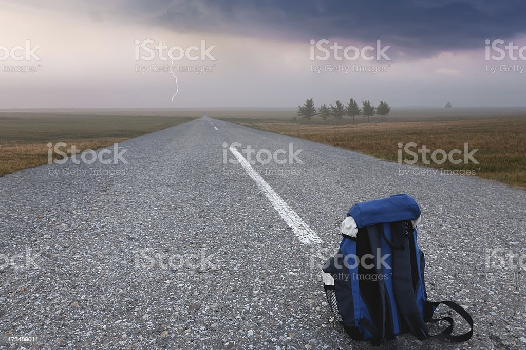 Backpack on empty road royalty-free stock photo