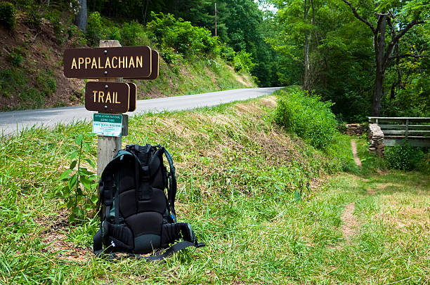 Backpack on the Appalachian Trail in southwest Virginia A backpacker's pack rest against a signpost for the Appalachian Trail in southwest Virginia. The road is state route 650, several miles from Marion, VA. The trail crosses the road and goes across the footbridge seen on the right. appalachian trail stock pictures, royalty-free photos & images