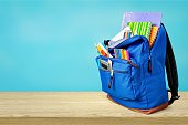 Colorful school supplies in backpack on blurred background