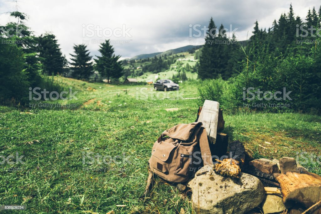 backpack with mobile phone in forest with car on background stock photo