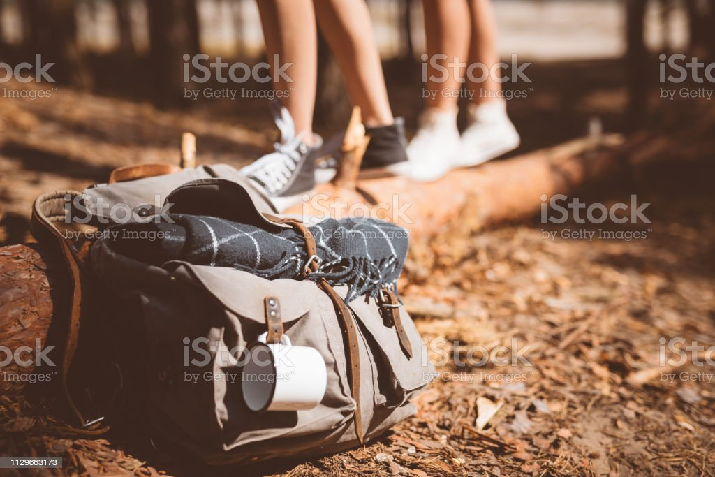 Backpack with mug and blanket in forest Close-up of backpack with cup and blanket. Low section of young female hikers are standing on fallen tree. Explorers are spending vacation in forest. 20-24 Years Stock Photo