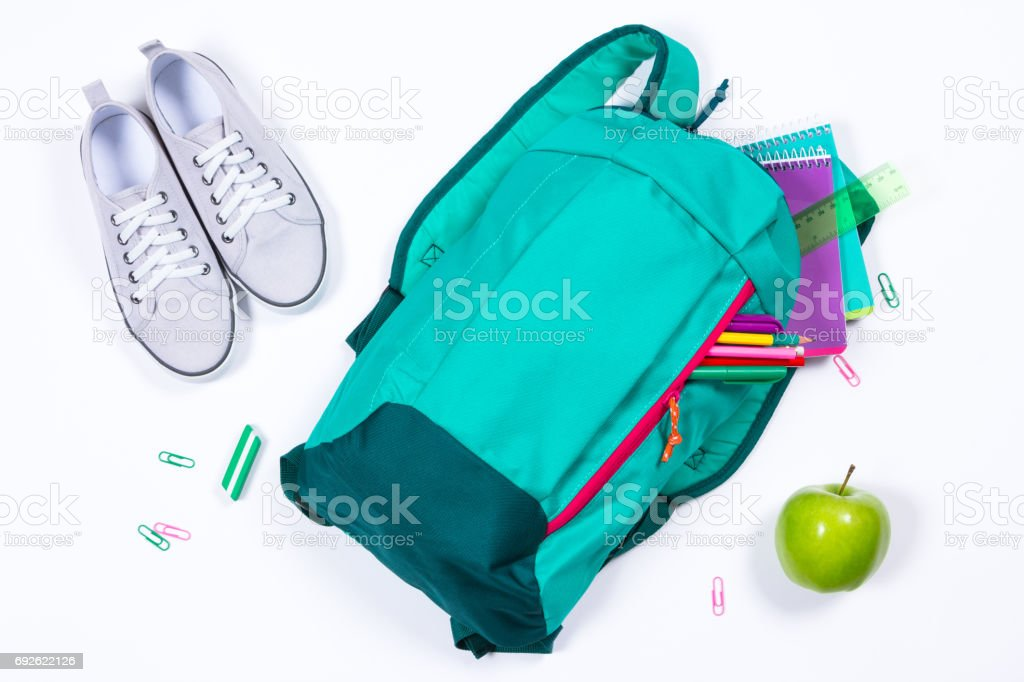 Backpack with school stationery on white background stock photo