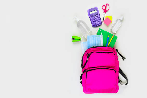Backpack with school supplies and COVID 19 prevention items. Top view, spilling onto a white background. stock photo