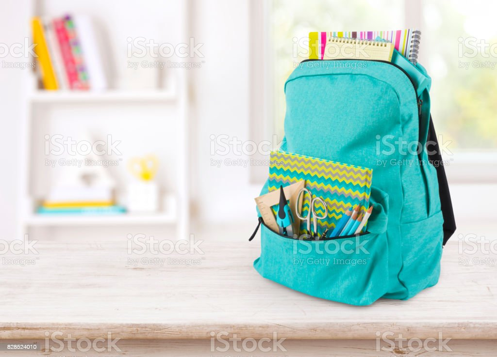 Backpack with school supplies on table over blurred educational interior royalty-free stock photo