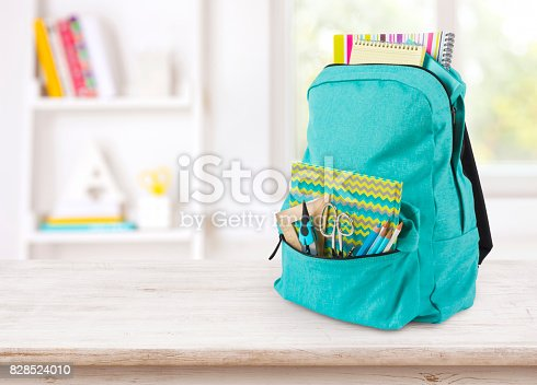 istock Backpack with school supplies on table over blurred educational interior 828524010