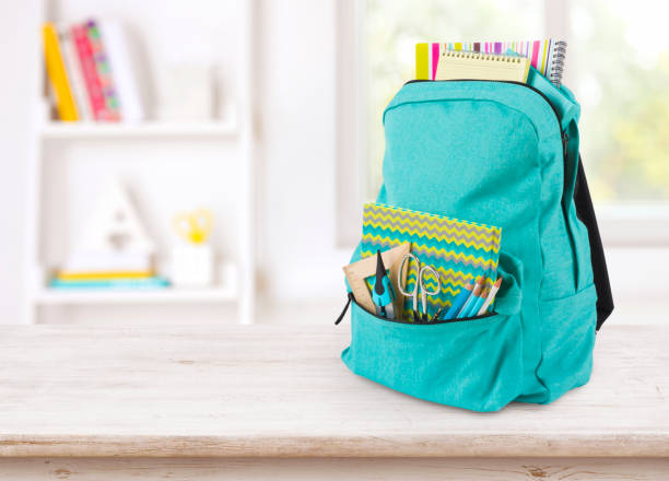 Backpack with school supplies on table over blurred educational interior stock photo