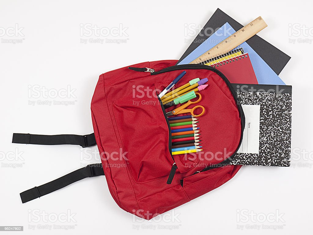 Backpack with school supplies spilling out stock photo