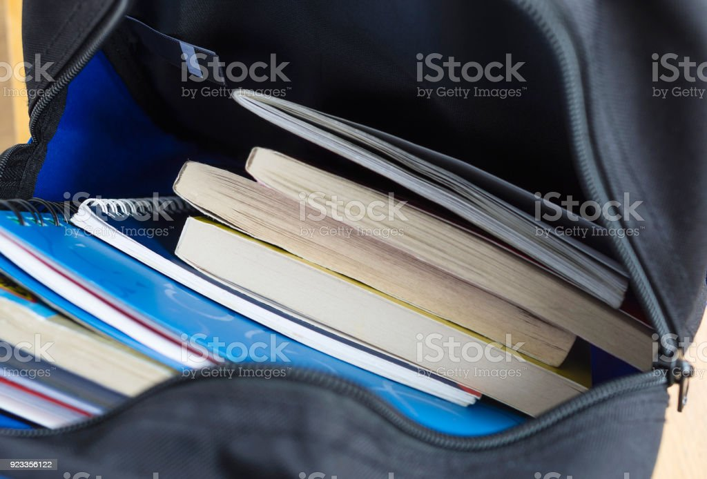 Backpack with schoolbooks and notebooks. Education concept image. Selective focus stock photo