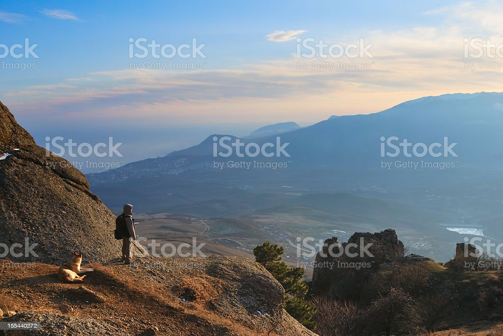 Backpacker and dog in the mountains stock photo