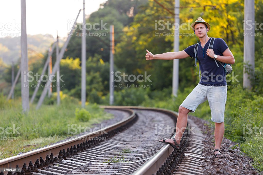 Backpacker catching Train on Countryside Railroad stock photo