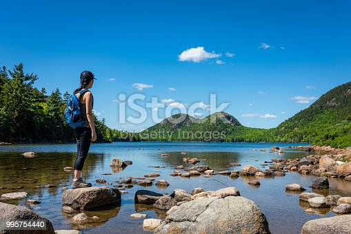 A female hiker exploring Jordan Pond in Acadia National Park, Maine.