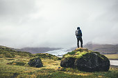 Backpacker standing on the rock and enjoying the view on Vatnajokull glacier in Iceland.