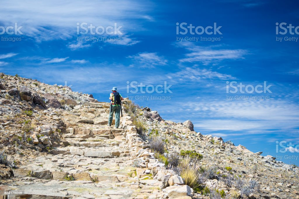 Backpacker exploring the majestic Inca Trails on Island of the Sun, Titicaca Lake, among the most scenic travel destination in Bolivia. Travel adventures and vacations in the Americas. Toned image. stock photo