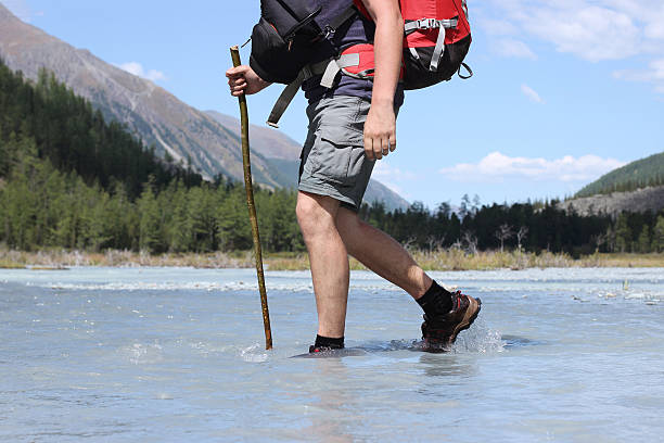 Backpacker go into the mountains. Mountain trekking. Man in harm stock photo
