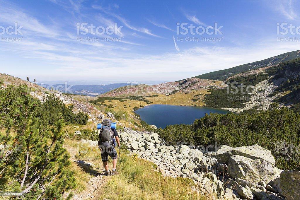 Backpacker going down towards mountain lake. stock photo