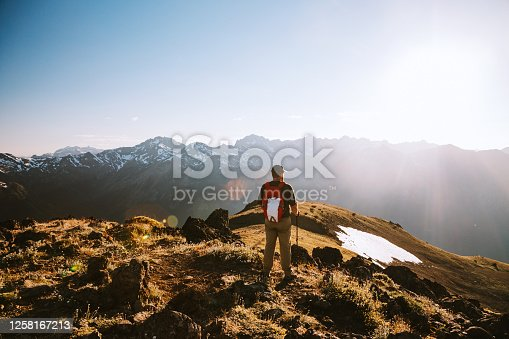 A lone mature adult hiker on a high ridge with a stunning sunset vista of the Olympic mountain range. Shot in Washington state on the Olympic Peninsula