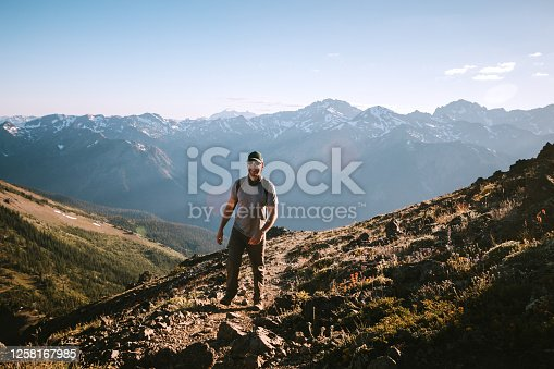 A lone hiker on a high ridge with a stunning sunset vista of the Olympic mountain range. Shot in Washington state on the Olympic Peninsula.
