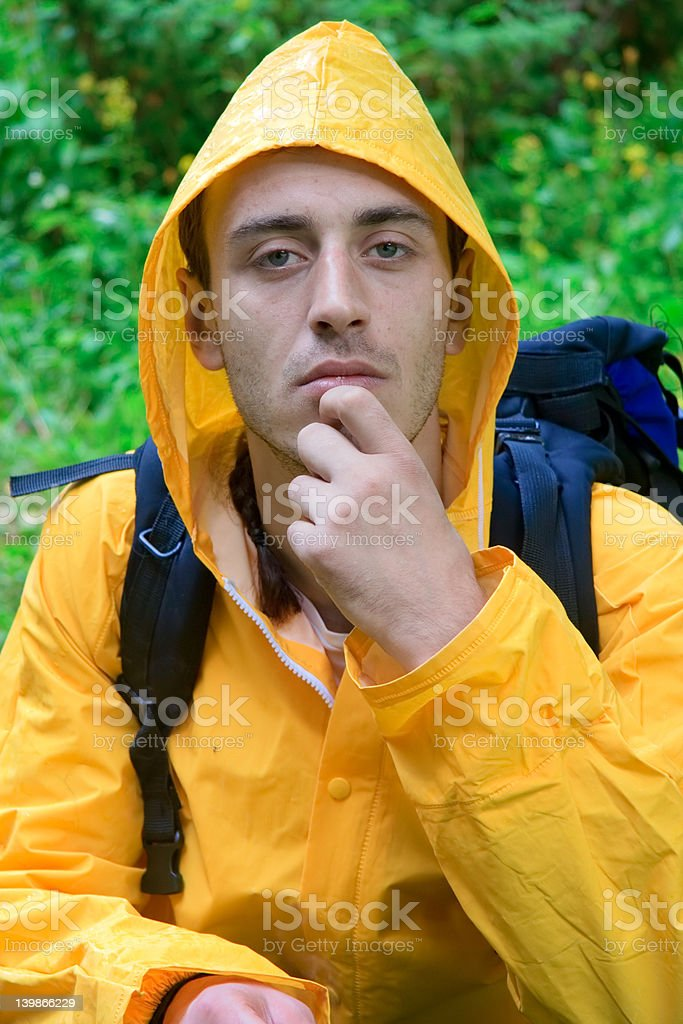 Backpacker in a yellow coat resting royalty-free stock photo