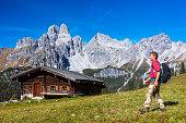 Backpacker in Alps with Mount Bischofsmütze in background