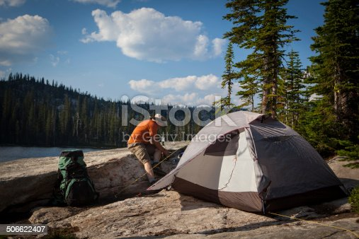 At his campsite alongside a mountain lake, a man is starting his stove in order to make dinner.