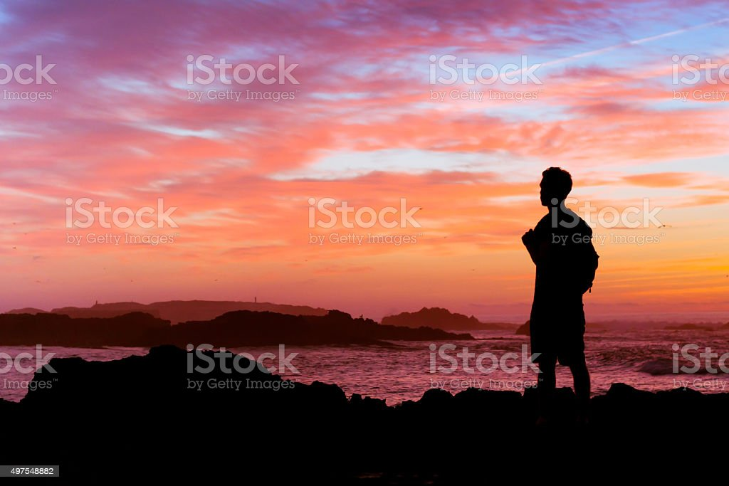 backpacker looking at sunset, silhouette, travel concept stock photo