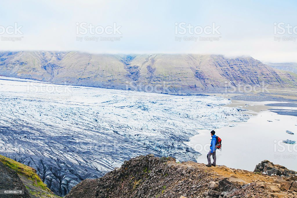 backpacker looking at the view of glacier in Iceland stock photo