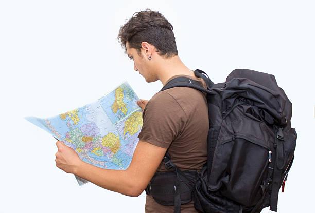 rucksacktourist schaut an weltkarte über weißer hintergrund - geführtes lesen stock-fotos und bilder
