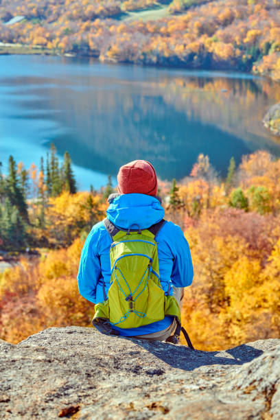 Backpacker man at Artist's Bluff in autumn Backpacker man hiking at Artist's Bluff in autumn. View of Echo Lake. Fall colours in Franconia Notch State Park. White Mountain National Forest, New Hampshire, USA white mountains new hampshire stock pictures, royalty-free photos & images