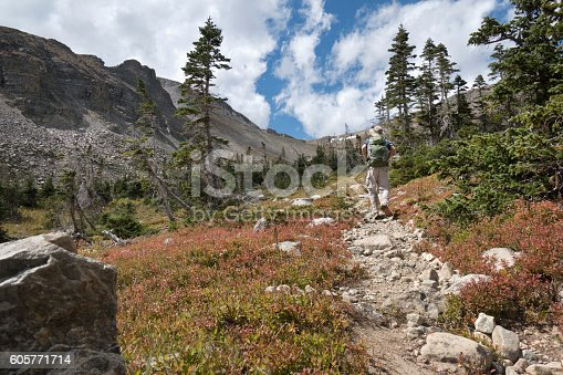 Hiking up a steep trail, a man with a backpack hikes towards the 11,837 foot high Buchanan Pass and the Rocky Mountain Continental Divide in the Indian Peaks Wilderness, Colorado.