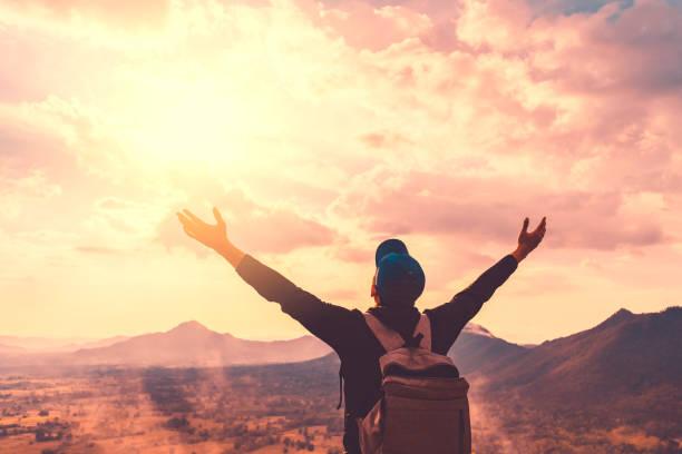 backpacker mann heben hand auf den berg mit sonnenuntergang himmel und wolken abstrakten hintergrund. - neue abenteuer stock-fotos und bilder