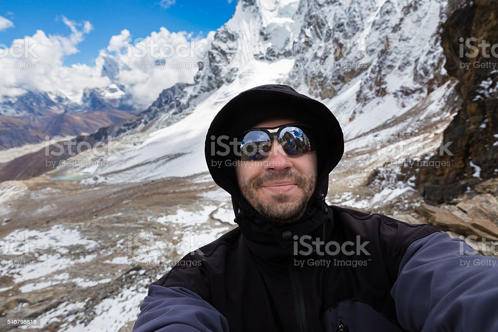 Backpacker man tourist mountaineer selfie. stock photo