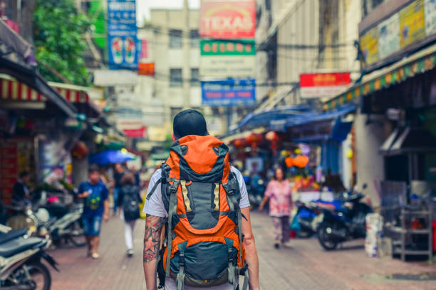 backpacker man walking in the street of asia. bangkok, thailand. - saccopelista foto e immagini stock