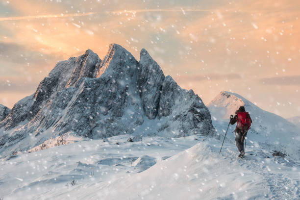 Backpacker mountaineer hiking on snow hill with majestic mount with snowfall at morning stock photo