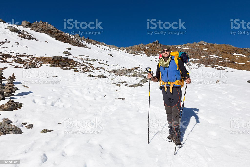 Backpacker mountaineer man standing rest snow mountain. stock photo