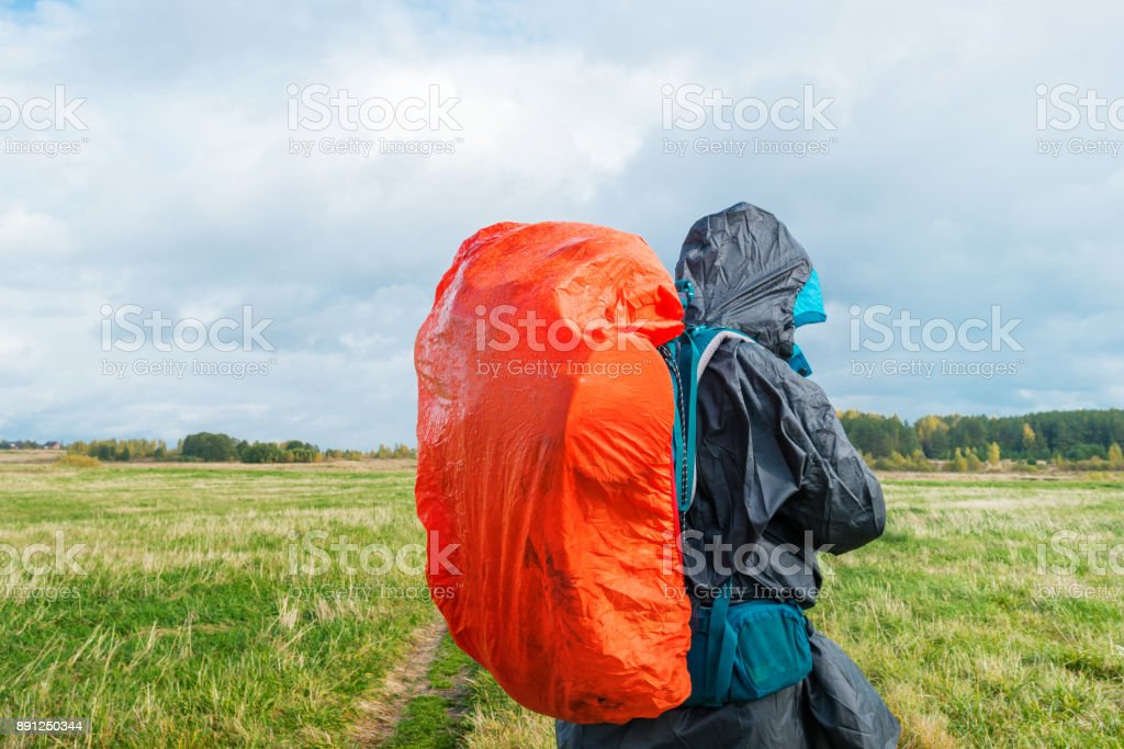 Backpacker on green field. Man hiking with bright red backpack. Autumn rural landscape. stock photo