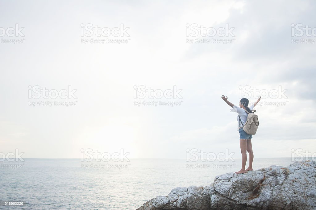 Backpacker on rock at beach at sunrise with arms raised. stock photo