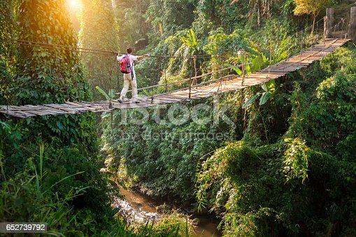 Backpacker on suspension bridge in rainforest