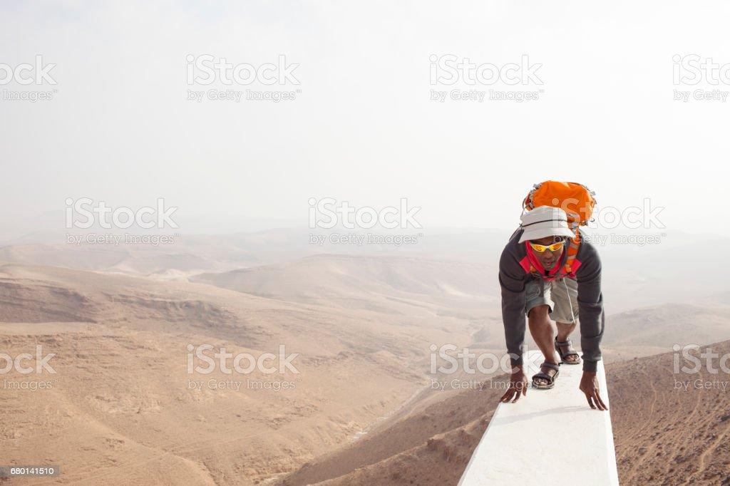 Backpacker ready to go trekking in desert mountains. stock photo