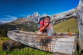 Backpacker refreshes at fountain with spring water in the Alps - Mount Bischofsmütze