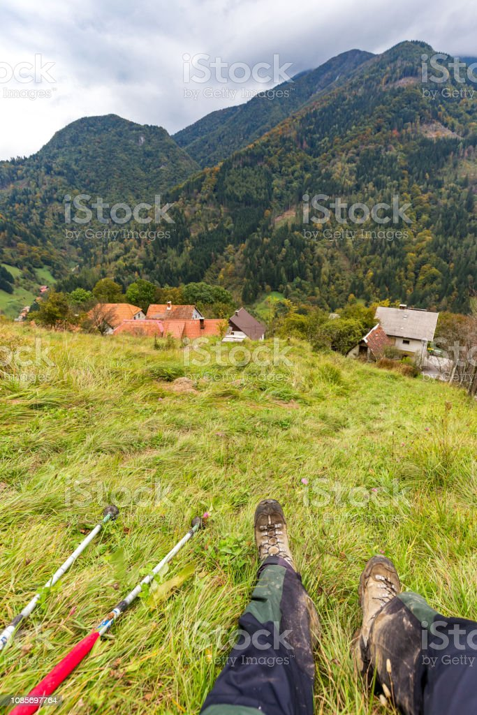 Backpacker resting mountain slope, forest village view. – zdjęcie