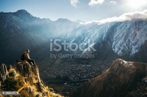 Young tourist in bright hat, black trousers with a backpack sit on cliff's edge and looking at the misty mountain village and glacier at sunrise, Stepantsminda, Georgia