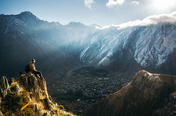 Backpacker sit on cliff edge and looks at mount valley - foto stock