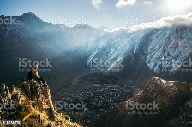 Photo of Backpacker sit on cliff edge and looks at mount valley