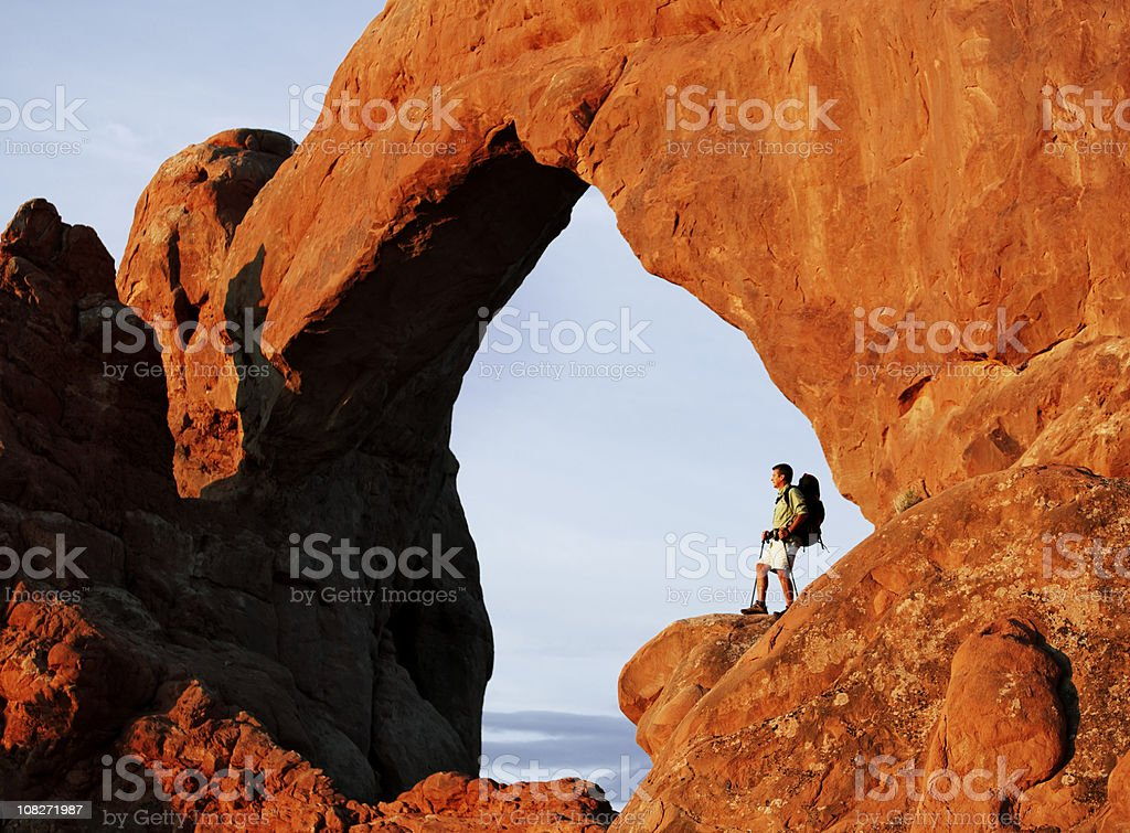 Backpacker Standing Below Arches Looking At View stock photo