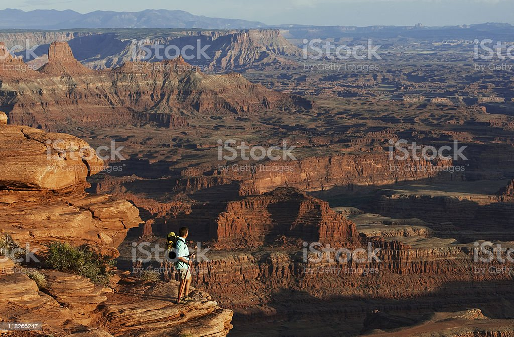 Backpacker  Standing On High Peak Looking Over Canyonlands National Park royalty-free stock photo