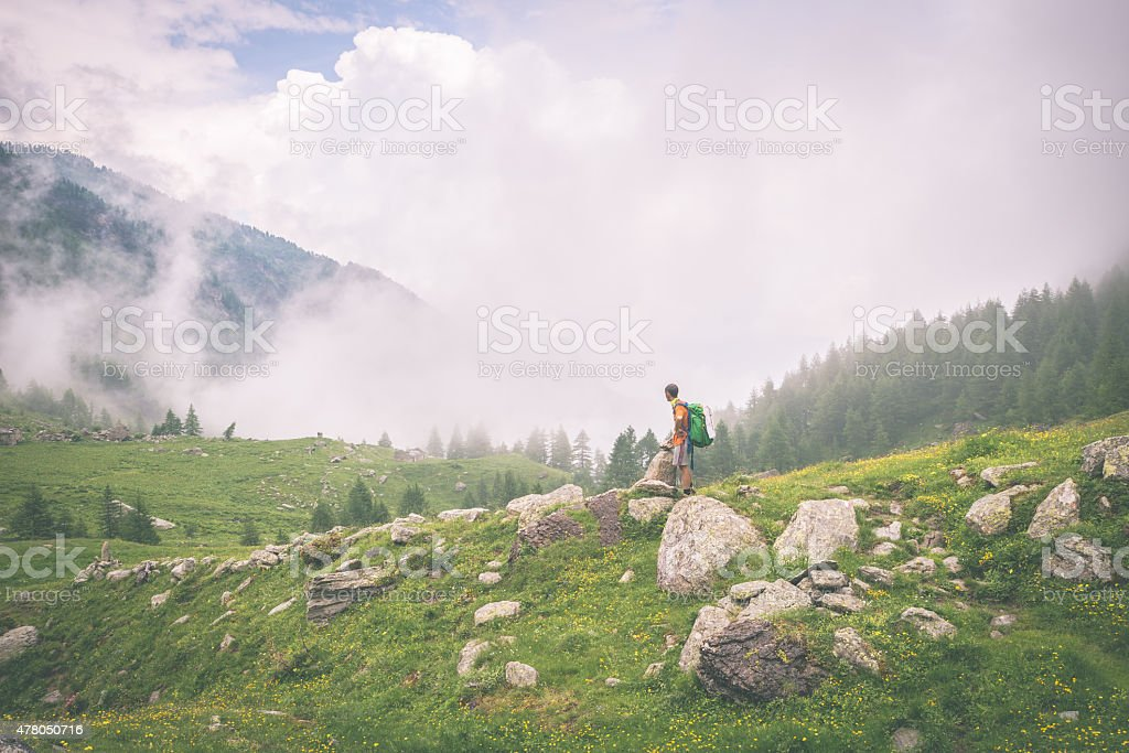 Backpacker standing on mountain footpath, toned stock photo